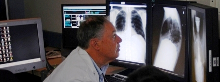 Radiologist reviewing electronic medical images on multiple monitors