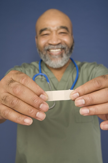 A smiling male nurse with bandaid.